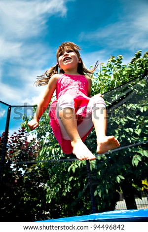 little girl jumping on the trampoline - stock photo