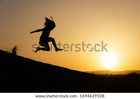 Little girl jumping over sand dunes on sunset in Maspalomas, Gran Canaria. Brave kid silhouette in the air at twilight in Canary Islands, Spain. No fear, courage, dare concepts ストックフォト ©