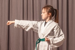 Little girl karate training. The girl trains to strike a taekwondo