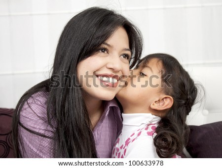 Little girl kissing her mommy in the home