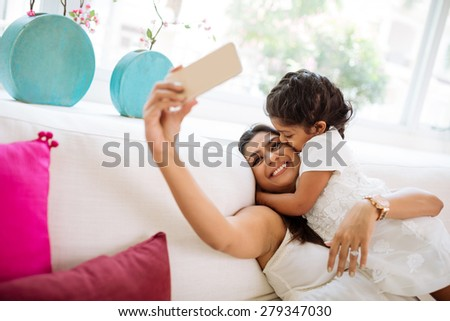 Little girl kissing her mother who is taking selfie