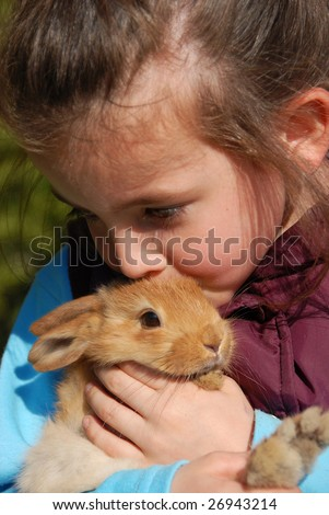 little girl kissing her young brown bunny. focus on the rabbit