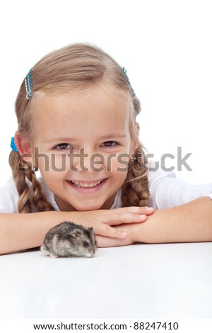 Little girl laughing and watching her hamster