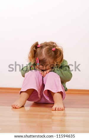 Little girl laying head on her knees