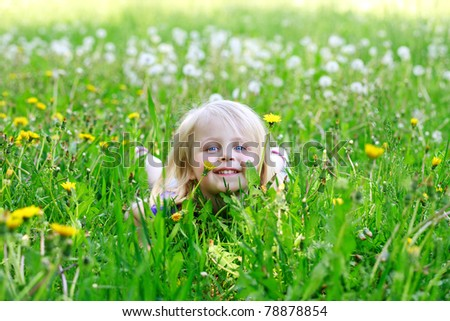 Little girl lays in dandelions outdoors smiling