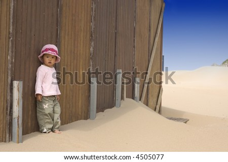 little girl leaning against a beach house - stock photo