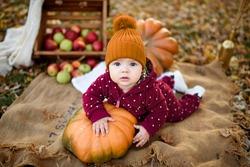 Little girl leans on a pumpkin.