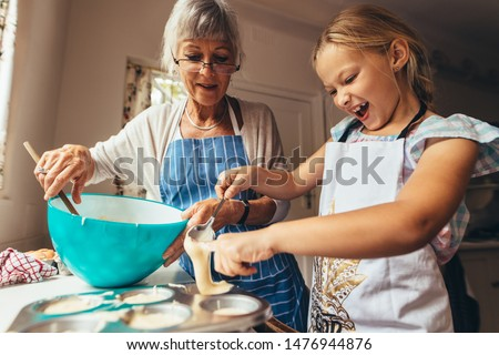 Little girl learning to make cup cakes with her grandmother. Excited girl pouring cake batter in cup cake moulds.