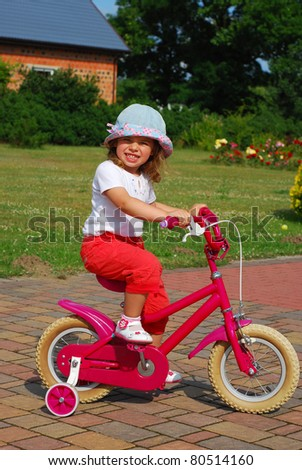 little girl learning to ride a bicycle with training wheels