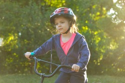 Little girl learns to ride bike in park near home. Portrait of a cute kid on bicycle. Happy smiling baby in helmet on cycling.