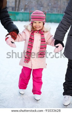 little girl learns to skate in the yard with older girlfriends