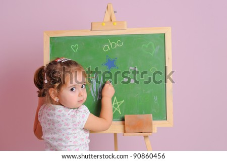 little girl learns to write with chalk