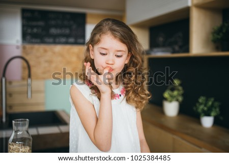 Little girl licking fingers after lunch