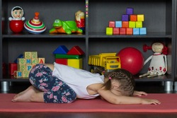 Little girl lie in extended child yoga pose as sit on heels, bring forehead down to rest in front of knees, place palm of hands flat out in front of her