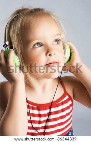 Little girl listening a music in earphones