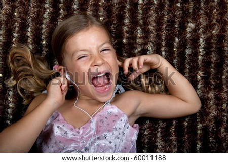 Little girl listening to music on headphones and screaming