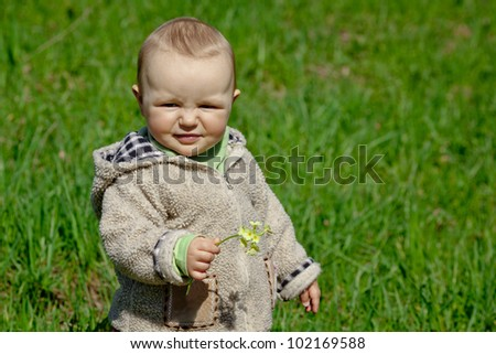 Little girl, little baby is a walk in the park. Is a sunny day and a beautiful lush grass. Spring.