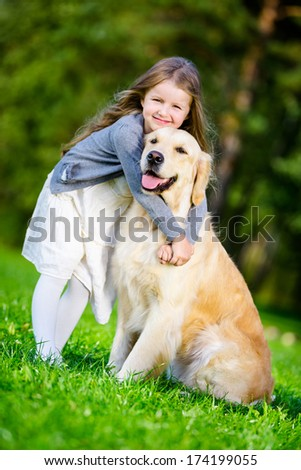 Little girl Little girl embraces golden retriever in the park