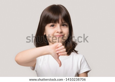 Little girl look at camera show thumb down gesture symbol of negative feedback and dislike, disagreement and rejection concept, head shot portrait six years old kid isolated on beige studio background #1410238706