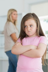 Little girl looking angry in the kitchen with mother in background