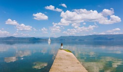 Little girl looking at a sailboat on the edge of a lake.  Standing on concrete bridge, back turned. Clouds and mountains reflecting in water. Blue. White clouds.  Landscape. Nature. Magical. Summer.