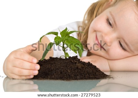 Little girl looking at a young plant wondering - closeup, isolated