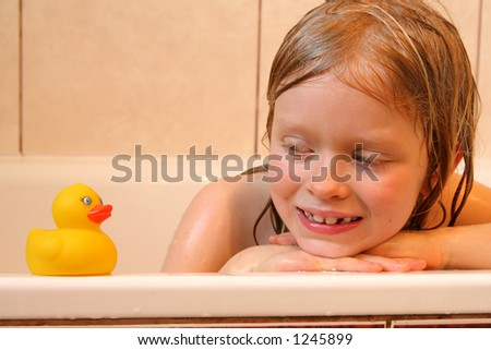 Little girl looking at bath duck