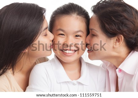 Little girl looking at camera while sister and grandmother kissing her