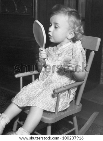 Little girl looking in mirror