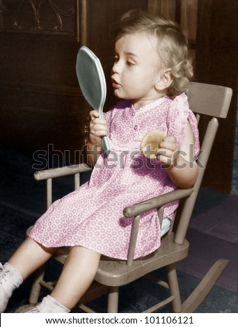 Little girl looking in mirror - stock photo