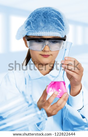 Little girl looking into a flask of red liquid