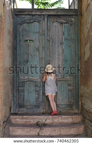 Little girl looking through a keyhole