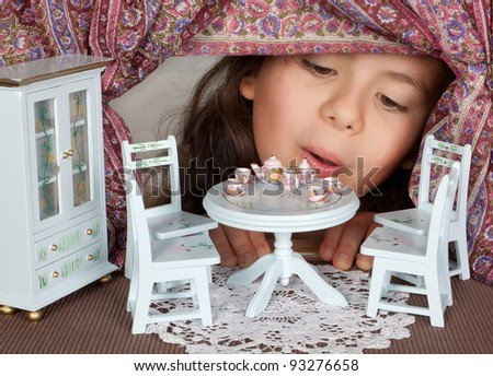 Little girl looking through a window into a doll's house like in alice in wonderland Stock photo ©