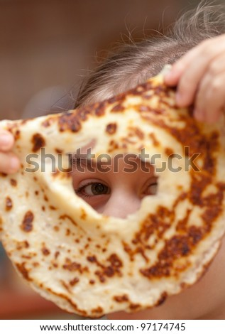 Little girl looking through the hole in pancake. Funny breakfast