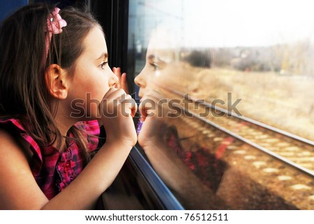 Shutterstock Little girl looking through window. She travels on a train.