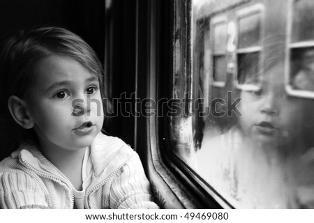 Little girl looking through window with reflections. She travels on a train.