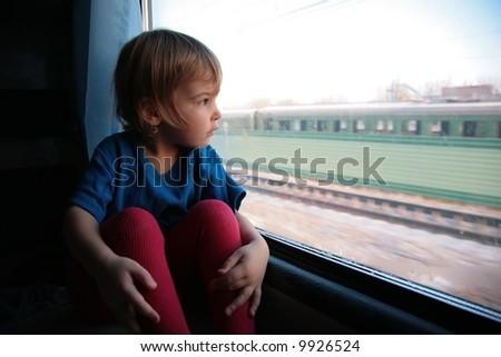little girl  looks in train`s window