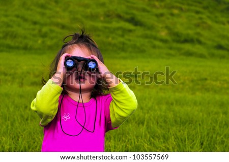 Little girl looks through binoculars isolated on green grass. Concept photo of child, children, outdoors, wildlife, nature, curiosity, exploration, knowledge, education, travel,aspirations, vacation. - stock photo