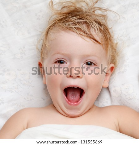 little girl lying in bed open-mouth closeup