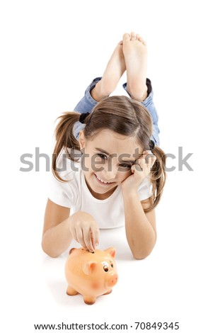 Little girl lying on floor and inserting a one euro coin on the piggy-bank