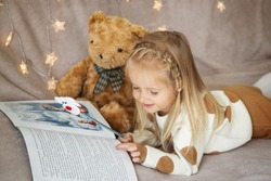 little girl lying on the couch at home and reading a children's winter wonderland, teddy bear sits next