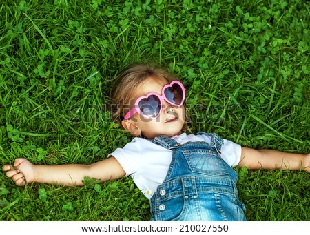 little girl lying on the grass in pink sunglasses, fashion style