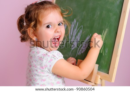Little girl makes a funny face as she draws on the blackboard