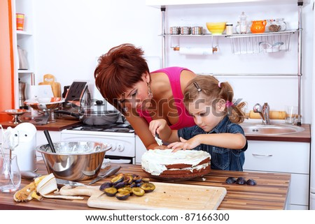Little girl making a fruit cake with her mother