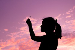 Little girl making a wish under the night sky, Shadow of a child holding a white grass flower under purple sky