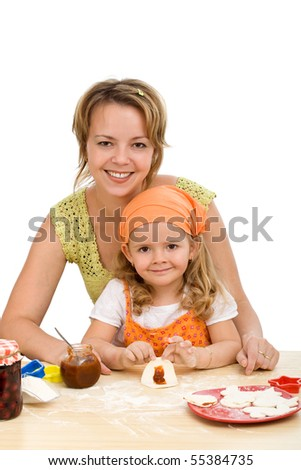 Little girl making cookies with her mother - isolated
