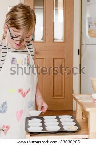 Little girl making fairy cakes