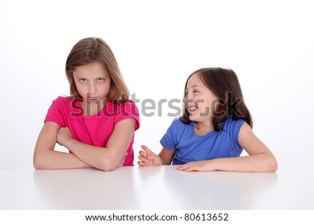 Little girl making fun of her sister - stock photo