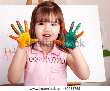 Little girl making hand-prints with paint.