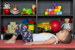 Little girl making yoga pose or exercise as lie on back with bent knees and feet flat on ground, rest arms down alongside body